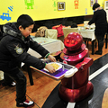 配膳専門ロボットからフレンチフライを受け取る少年