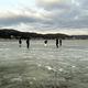 結氷した湖面の上に出て氷の状態を調べる八剱神社の総代ら=16日朝