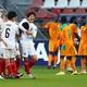 ゴールを決めた植田を祝福する日本代表と、がっくりと肩を落とすコートジボワール代表。 (C)Getty Images