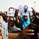 スーダン・ハルツームの広場グリーン・ヤードで、犠牲者の一人の肖像画を掲げるデモの参加者ら(2019年7月18日撮影)。(c)AFP=時事/AFPBB News