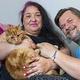 6週間かけて旅した猫を抱く元の飼い主(画像は『The Sun 2020年8月3日付「A FUR OLD TREK Ginger tabby cat Garfield travels 40 MILES over seven weeks to find former owners after they rehomed him」(Credit: JOHN McLELLAN)』のスクリーンショット)