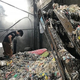 ごみから集めたプラスチックを「洗浄」「加熱」「冷却」して再びプラスチック原料にする工程を手作業でする人たち=ベトナム北部ミンカイ村