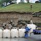 地震の影響で崩落した駐車場ののり面の前に設置された土のう=19日午後、新潟県村上市