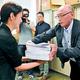 (写真)寄せられた署名の束を手渡す井口さん(右)=19日、愛知県庁