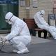 23日、韓国南部・大邱市の病院で、新型コロナウイルス対策で防護服を着用し、救急車を待つ医療関係者(AFP時事)
