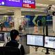 1月4日、香港国際空港に到着した旅行者の健康状態を監視する担当者=AP